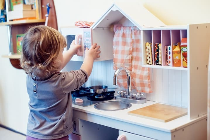 toddler playing pretend kitchen