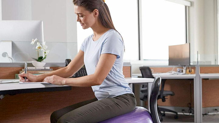 women with support back brace sitting on pilates ball