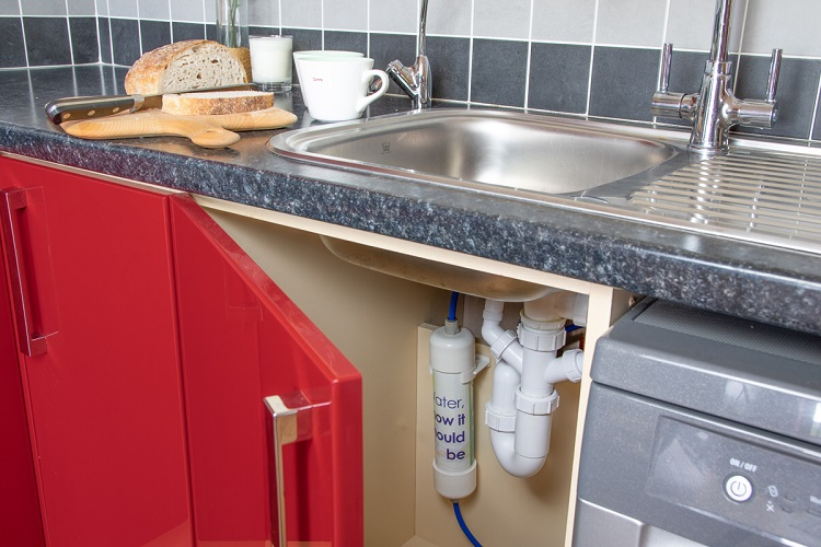 picture of a kitchen sink, board with bread, teacups, corner of a washing machine and red appliances with under sink water filter