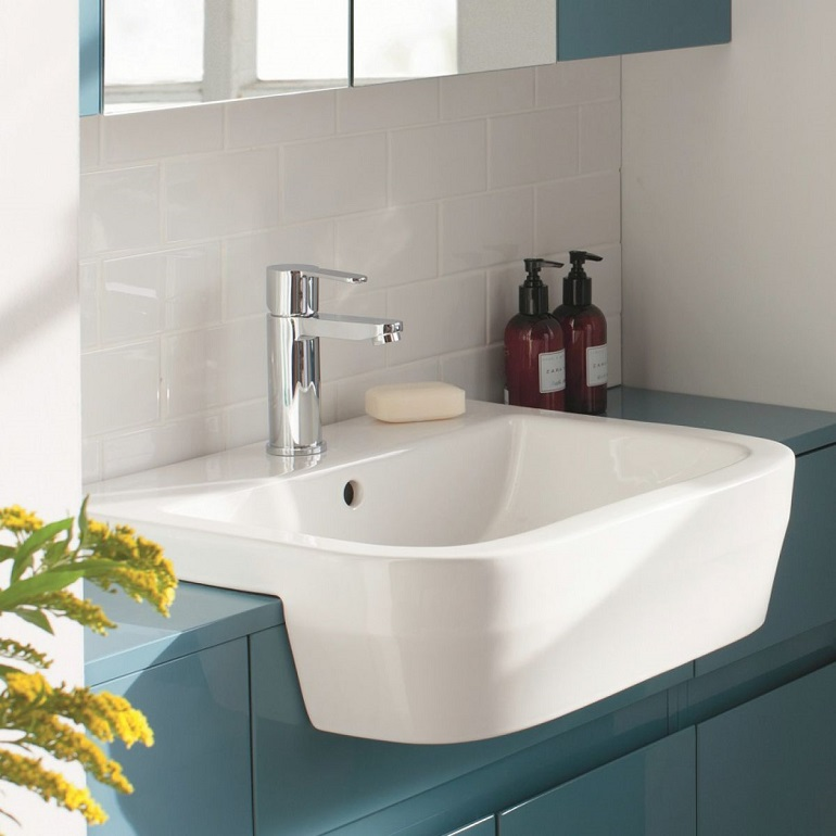 picture of a bathroom with blue cabins, white tiles and a semi recessed vanity basin
