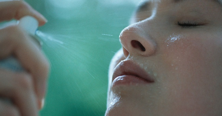 picture of a persons putting mist on the face