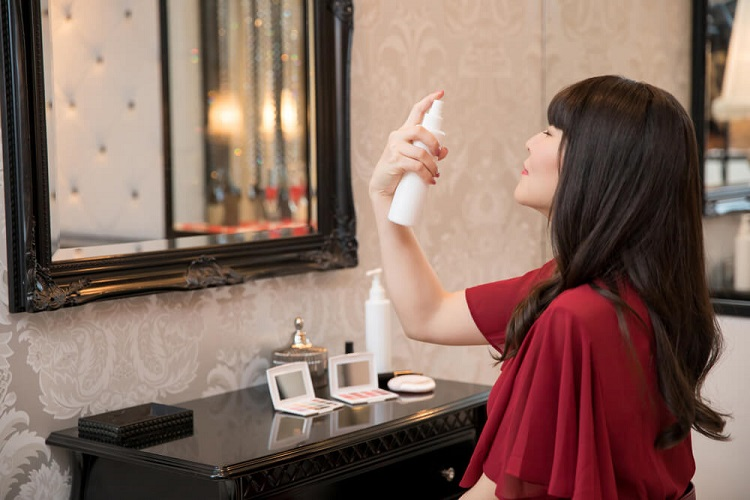 picture of a woman in front a mirror with some makeup, putting a mist on her face