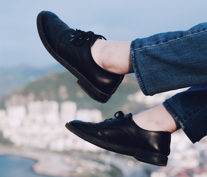 picture of person in black dance shoes above the city