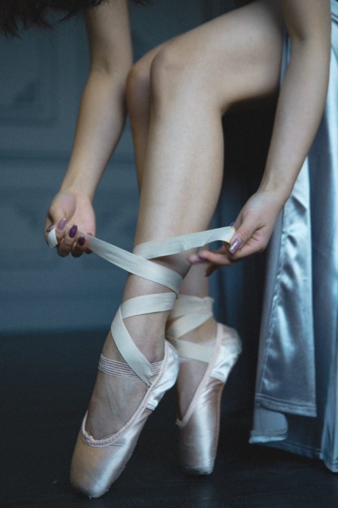 picture of a person putting on a ballerina  shoes